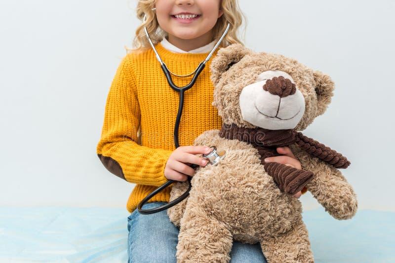 petite fille de sourire avec le stéthoscope écoutant le nounours images libres de droits
