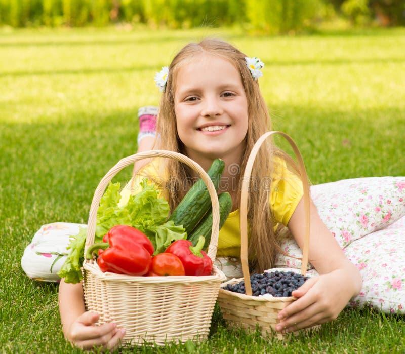Petite fille de sourire avec les légumes et la baie image libre de droits