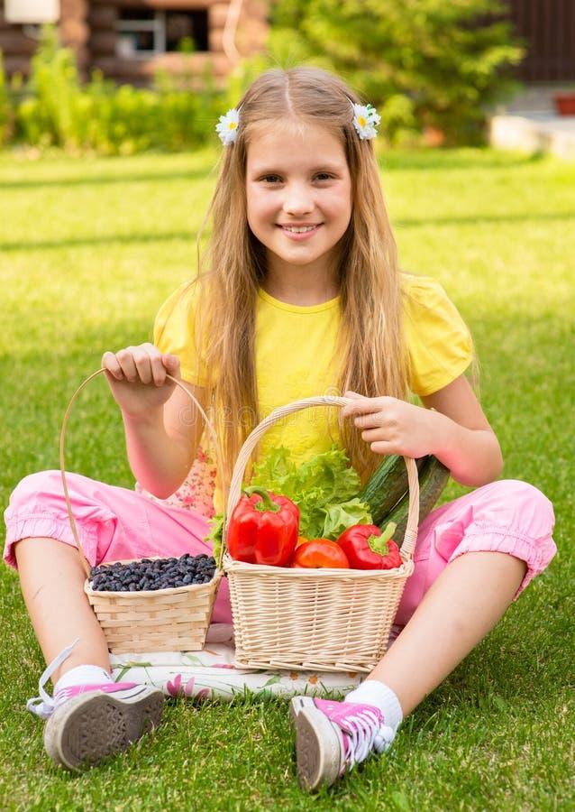 Petite fille de sourire avec les légumes et la baie image stock