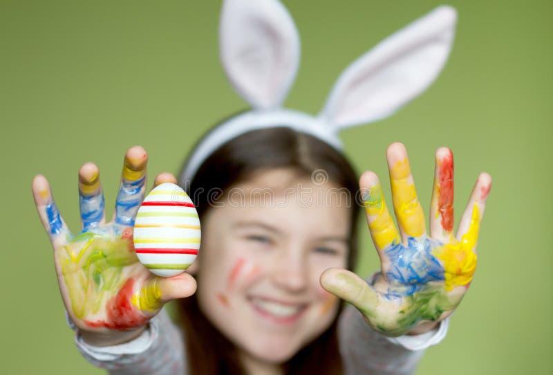 Petite fille de sourire avec les oeufs de pâques colorés photo stock