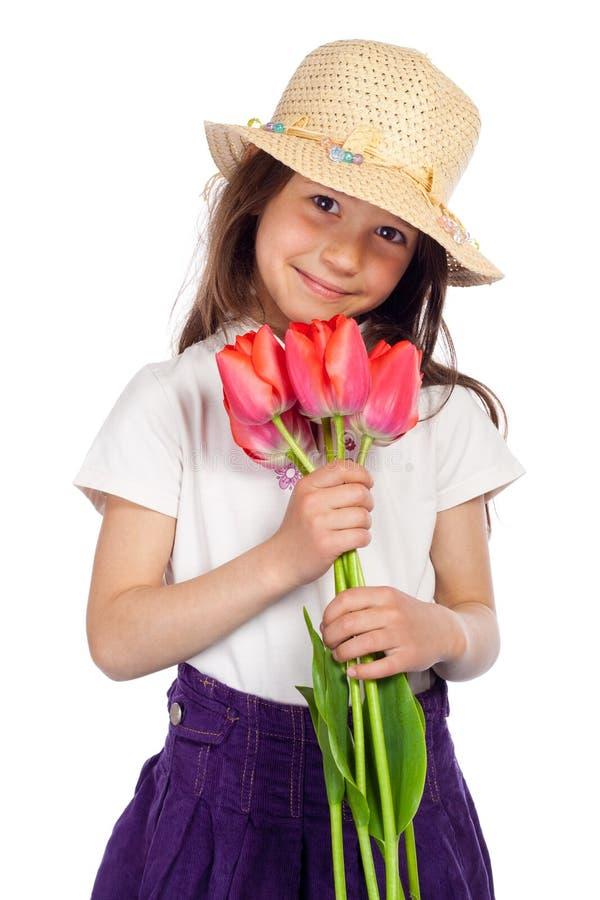 Petite fille de sourire avec les tulipes rouges photographie stock libre de droits