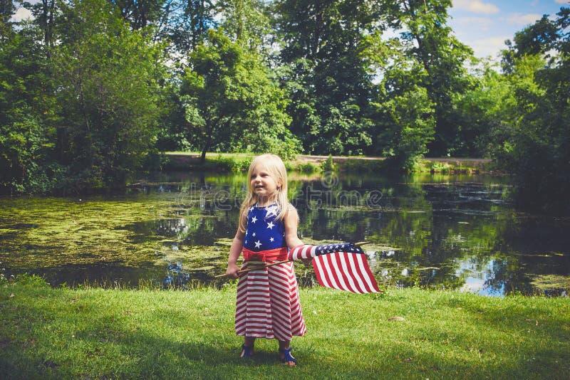 Petite fille de sourire avec tenir le drapeau américain image libre de droits
