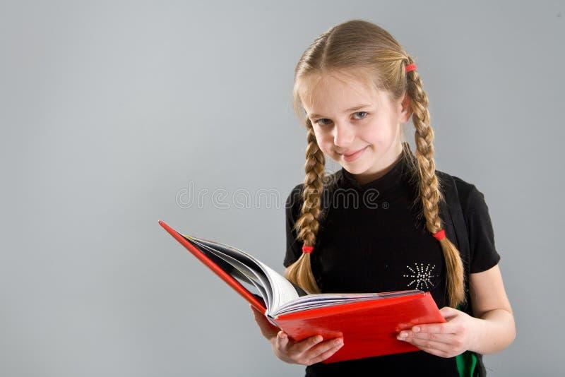 Petite fille de sourire avec un livre photographie stock