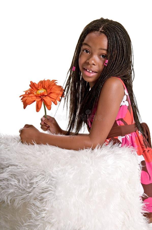 Petite fille de sourire avec une fleur photo libre de droits