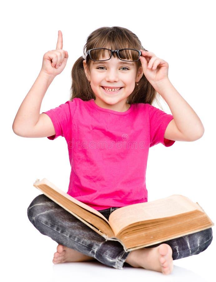 Petite fille de sourire d'étudiant dans des lunettes avec le livre et le doigt  isolayed sur le blanc images libres de droits