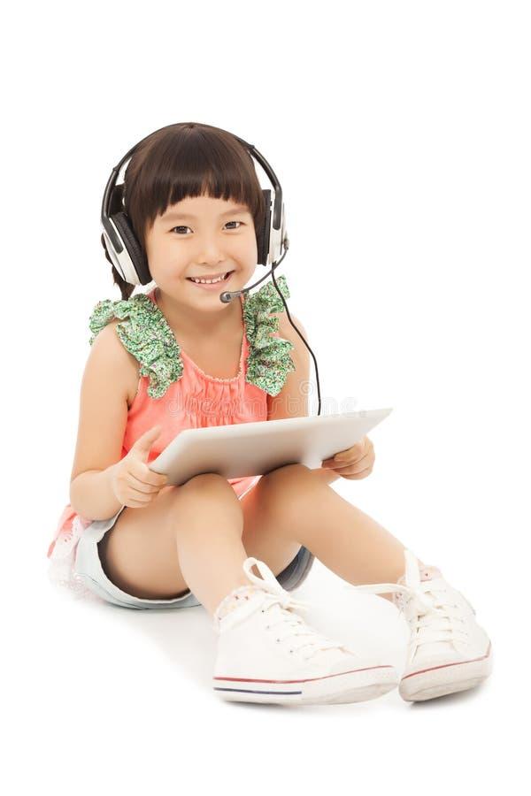 Petite fille de sourire d'étudiant reposant et tenant un comprimé photo libre de droits