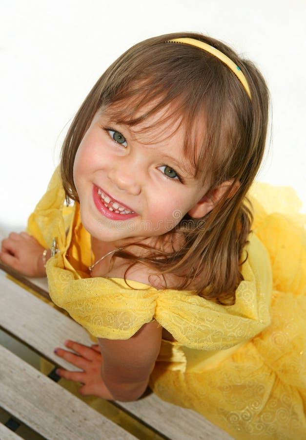 Petite fille de sourire dans la robe jaune image stock