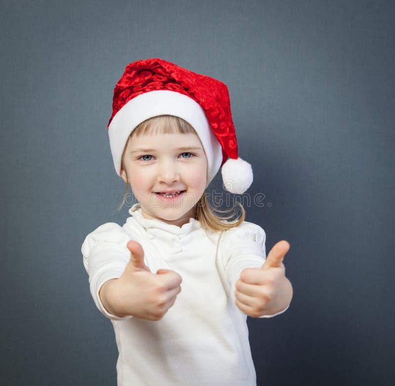 Petite fille de sourire dans le chapeau de Santa montrant des pouces  images stock