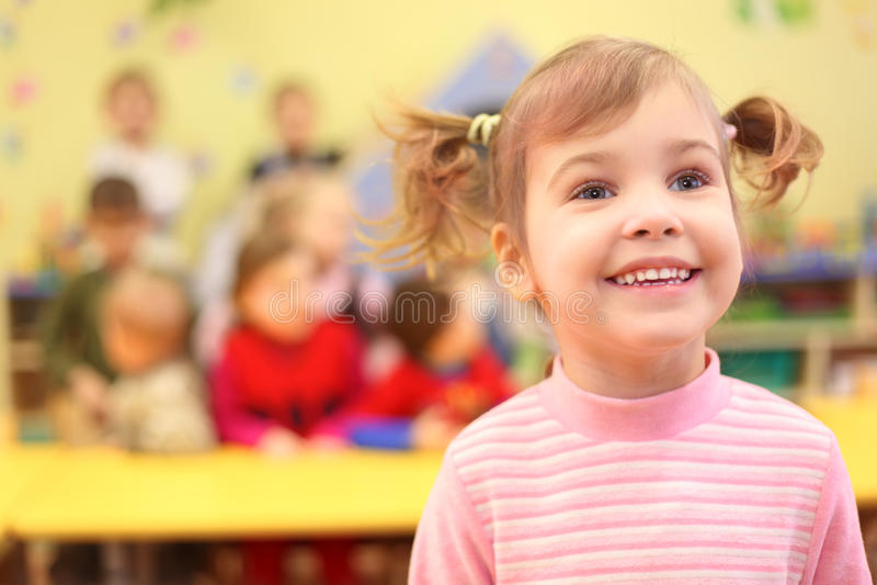 Petite fille de sourire dans le jardin d'enfants images stock