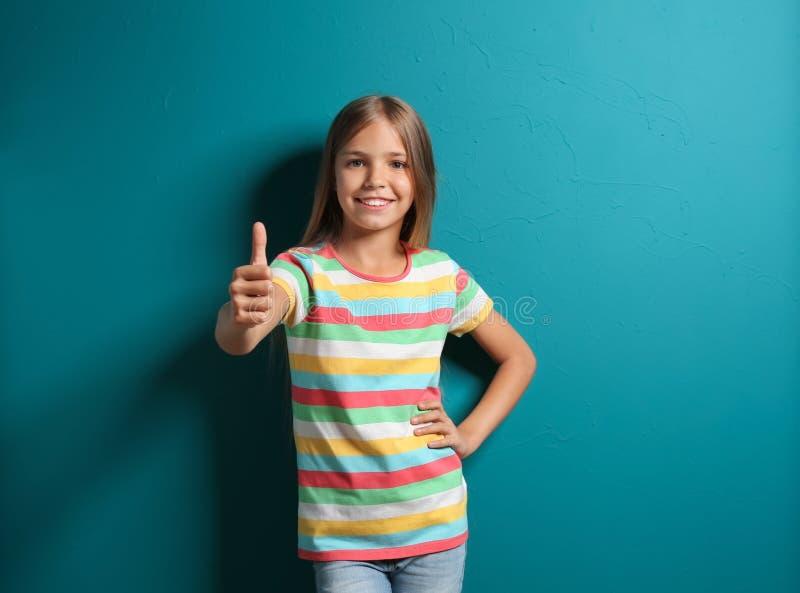Petite fille de sourire dans le pouce- d'apparence de T-shirt sur le fond de couleur image stock