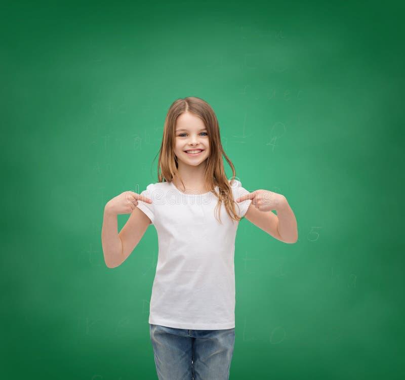 Petite fille de sourire dans le T-shirt blanc vide photographie stock libre de droits