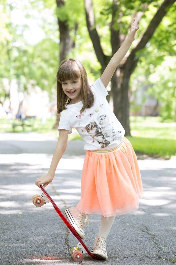 Petite fille de sourire dans une jupe avec une planche à roulettes en parc images stock