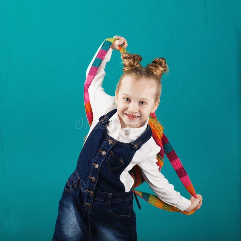 Petite fille de sourire drôle avec le grand sac à dos sautant et ayant f images stock