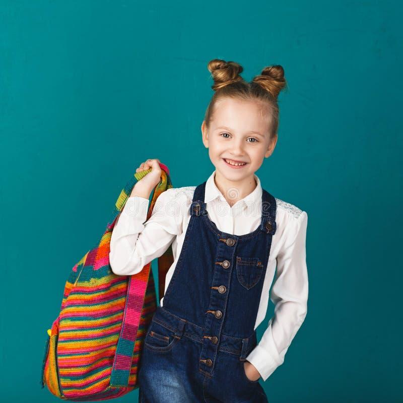 Petite fille de sourire drôle avec le grand sac à dos sautant et ayant f image libre de droits
