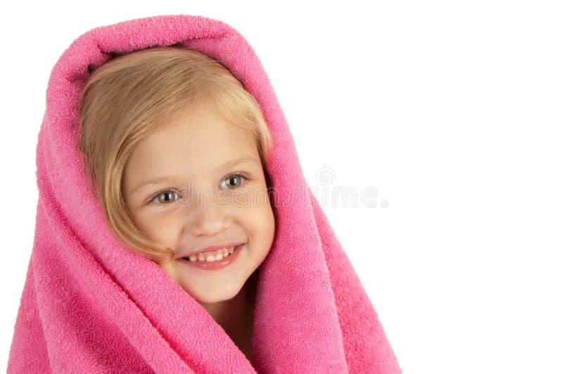Petite fille de sourire enveloppée dans un essuie-main rose photos stock