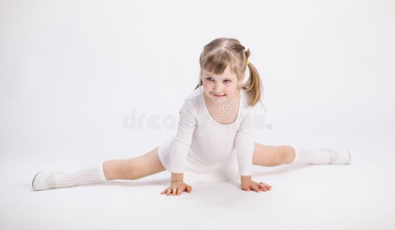 Petite fille de sourire faisant les fentes image stock