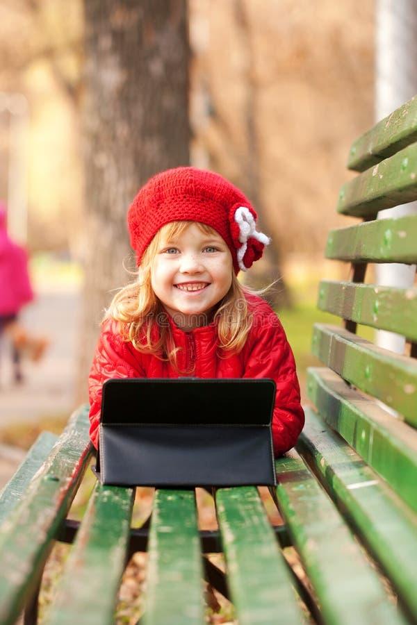 Petite fille de sourire heureuse avec le PC de comprimé photos stock