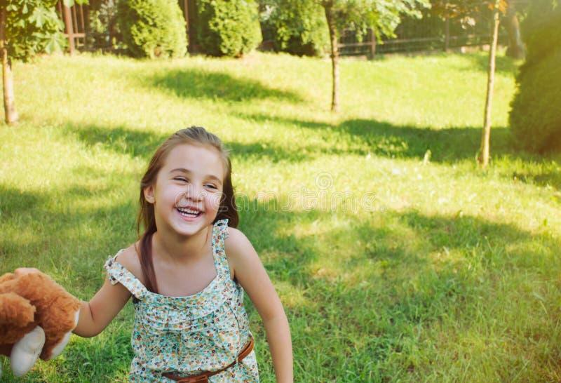 Petite fille de sourire heureuse jouant avec le jouet dans le jardin d'enfants i images libres de droits
