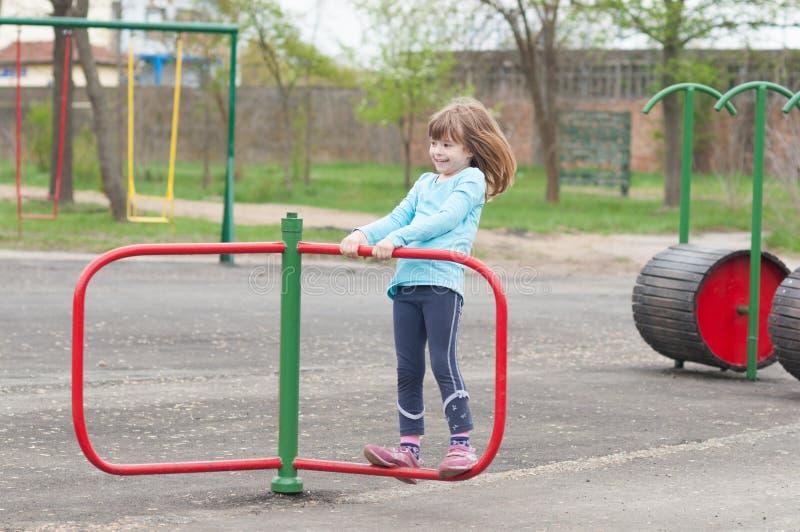 Petite fille de sourire heureuse jouant sur le terrain de jeu au printemps image stock