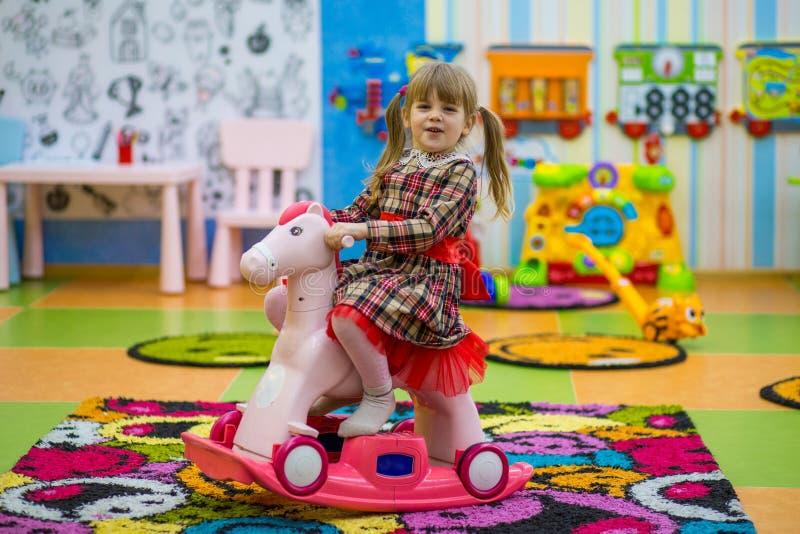 Petite fille de sourire heureuse montant une oscillation en bois de cheval photographie stock