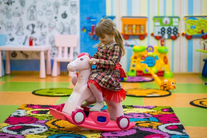Petite fille de sourire heureuse montant une oscillation en bois de cheval photo stock