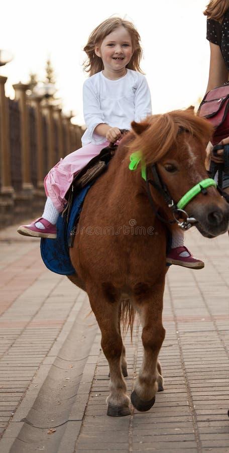Petite fille de sourire heureuse sur un poney images stock