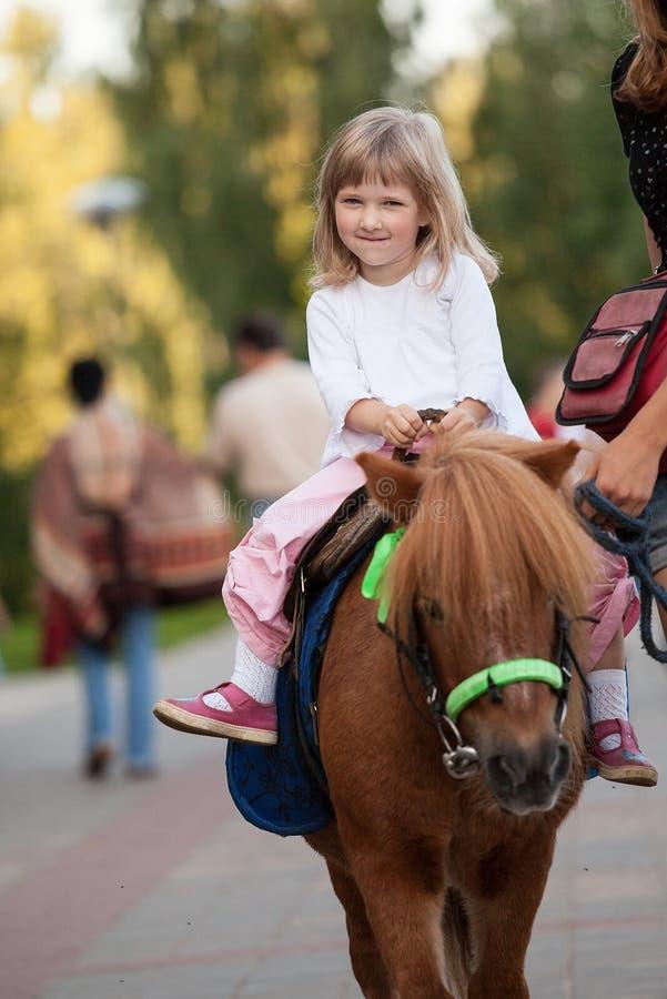 Petite fille de sourire heureuse sur un poney photo libre de droits