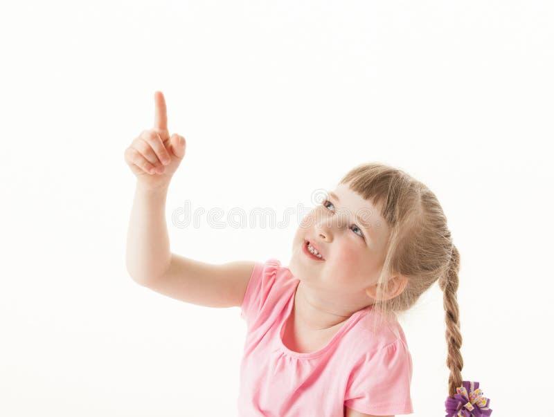 Petite fille de sourire indiquant quelque chose  photos stock