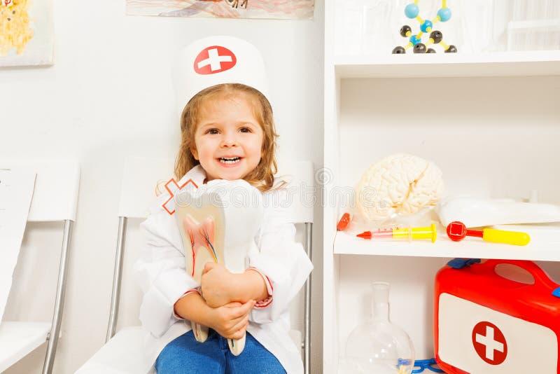 Petite fille de sourire jouant le dentiste au coffret photos stock