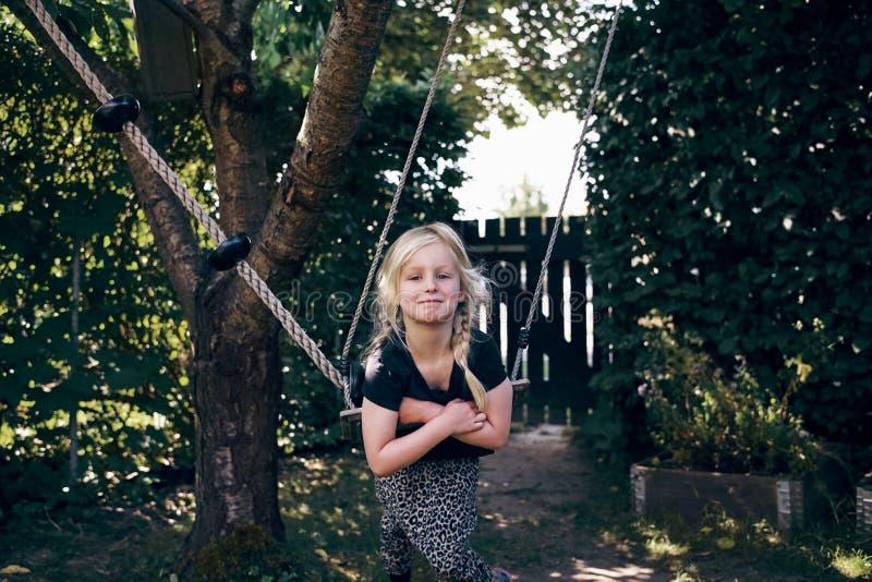 Petite fille de sourire jouant sur un extérieur d'oscillation d'arbre photos libres de droits