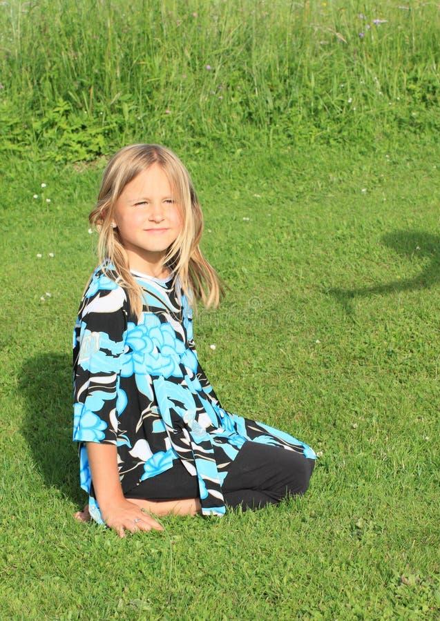 Petite fille de sourire kneeing sur l'herbe photographie stock libre de droits