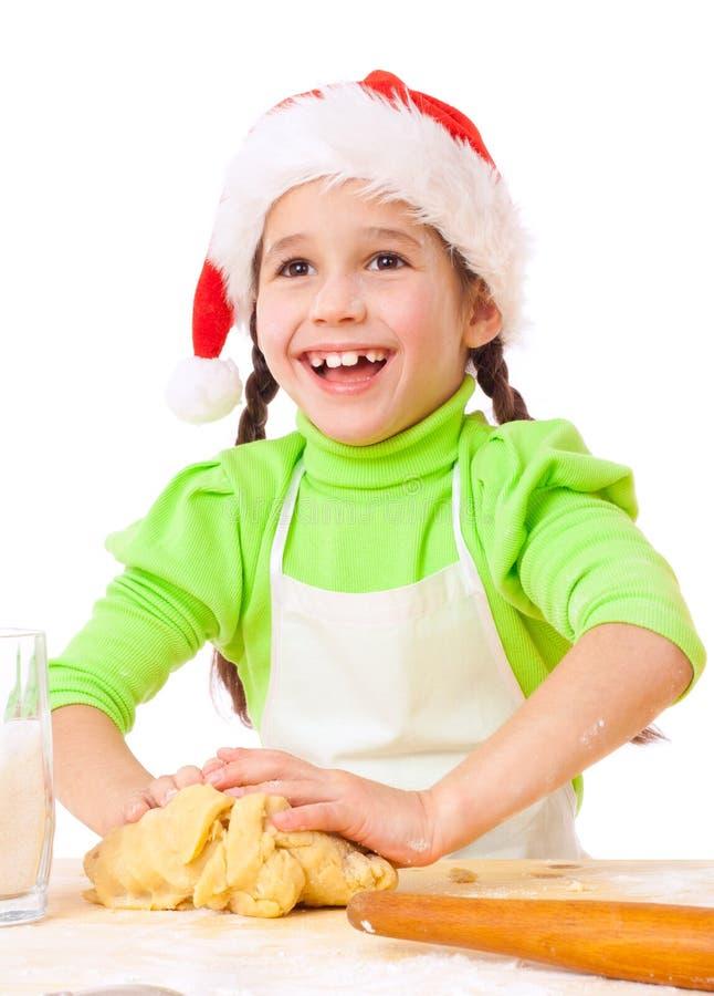 Petite fille de sourire malaxant pour la cuisson de Noël images stock