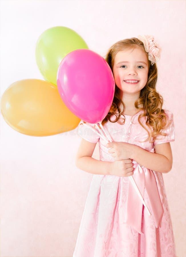 Petite fille de sourire mignonne avec des ballons images libres de droits