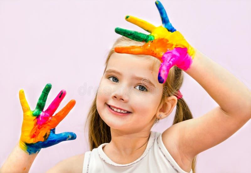 Petite fille de sourire mignonne avec des mains en peinture photographie stock
