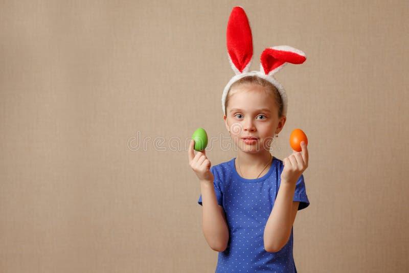 Petite fille de sourire mignonne avec les oeufs de pâques colorés Joyeuses Pâques image stock
