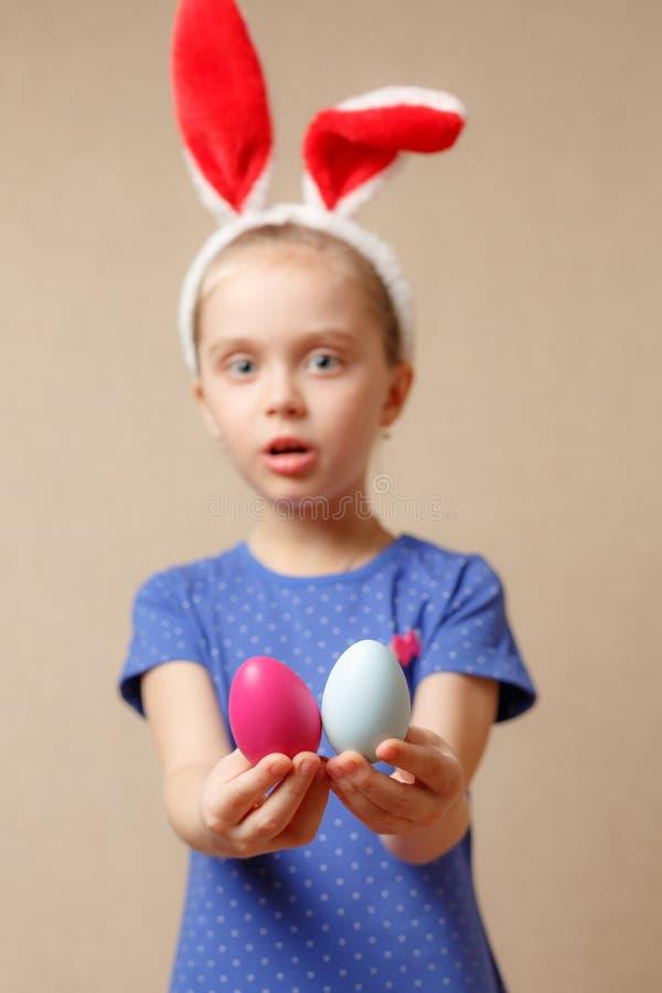 Petite fille de sourire mignonne avec les oeufs de pâques colorés Joyeuses Pâques Foyer sélectif photo libre de droits