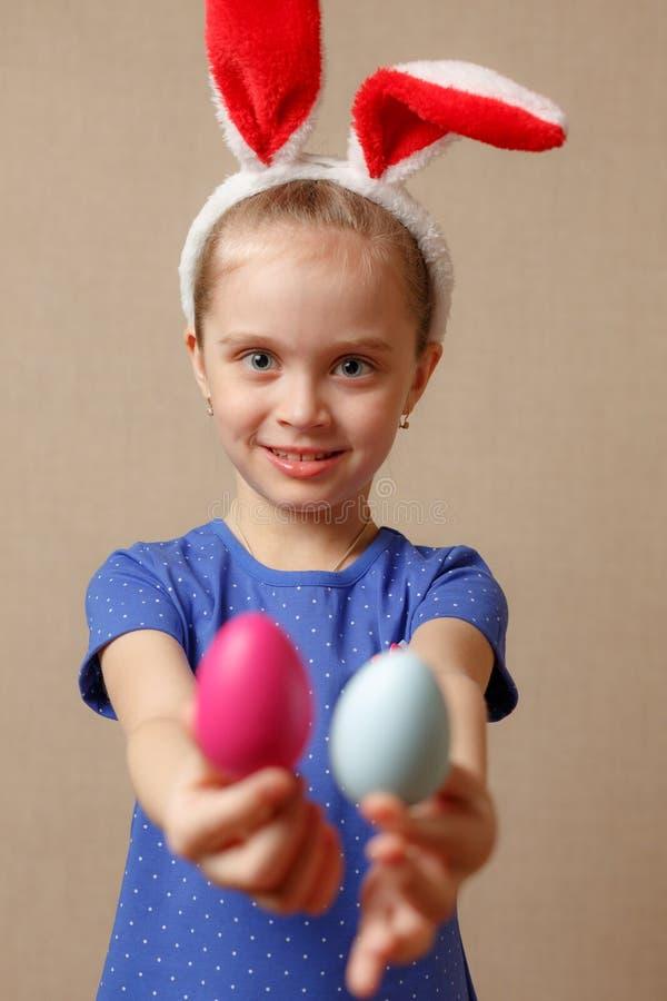 Petite fille de sourire mignonne avec les oeufs de pâques colorés Joyeuses Pâques Foyer sélectif photographie stock libre de droits