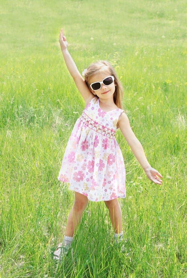 Petite fille de sourire mignonne dans des lunettes de soleil sur le pré images libres de droits
