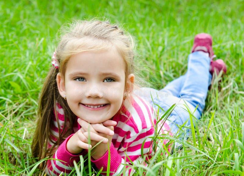 Petite fille de sourire mignonne se situant dans l'herbe sur le pré photos libres de droits
