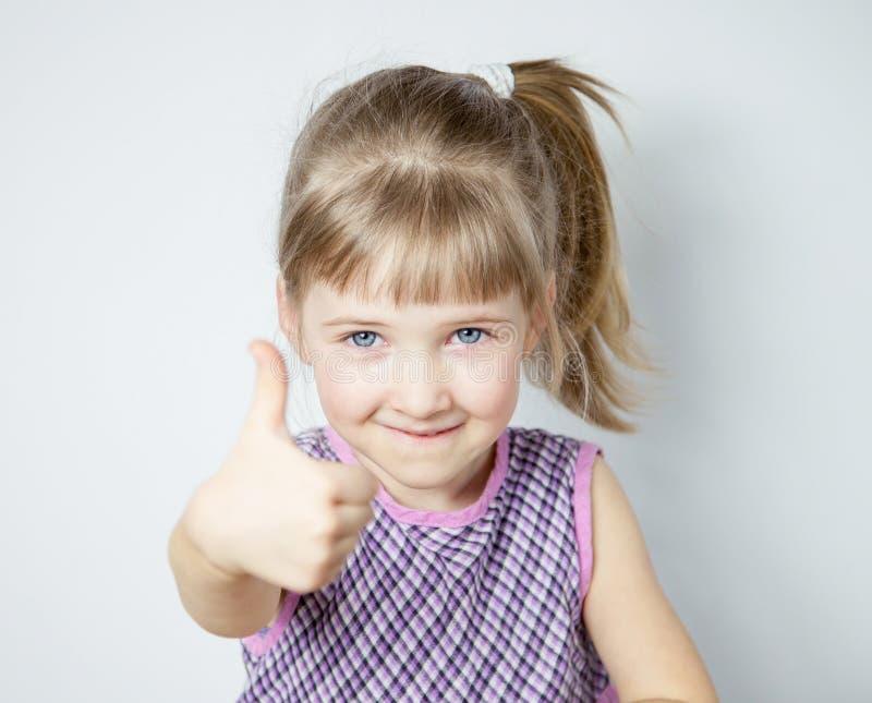 Petite fille de sourire montrant le pouce  photographie stock libre de droits