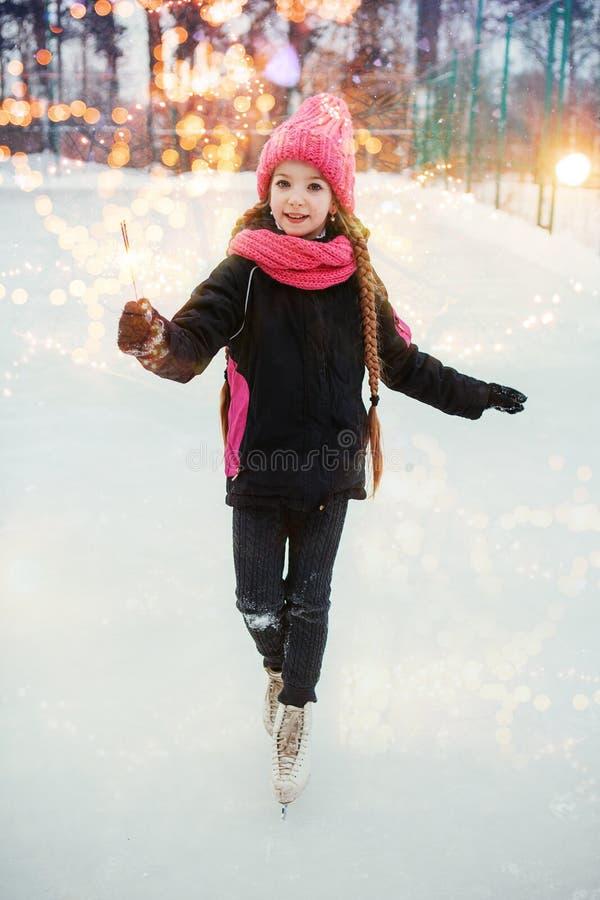Petite fille de sourire patinant sur la glace et tenant la lumière de Bengale dans l'usage rose extérieur photo stock