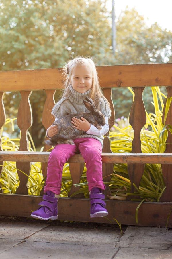 Petite fille de sourire posant dans l'axe avec le lapin photo stock