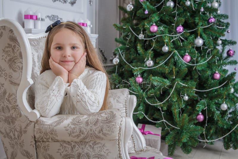 Petite fille de sourire près de fauteuil se reposant d'arbre de Noël photos stock