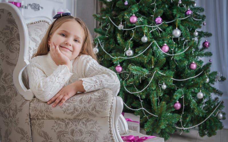Petite fille de sourire près de l'arbre de Noël se reposant dans le fauteuil image stock