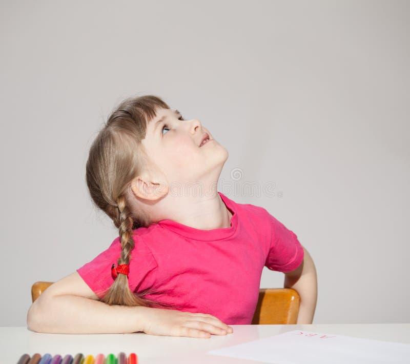 Petite fille de sourire s'asseyant à la table et recherchant images stock