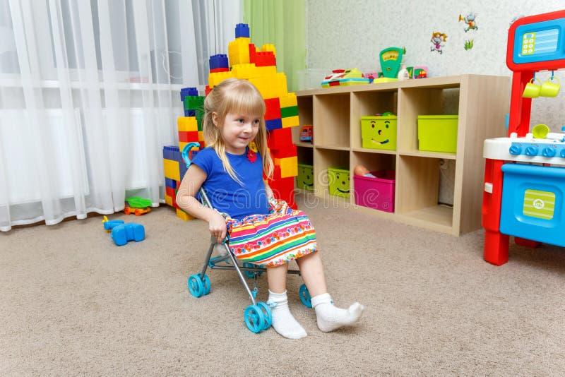 Petite fille de sourire s'asseyant dans la poussette de jouet à la maison image stock