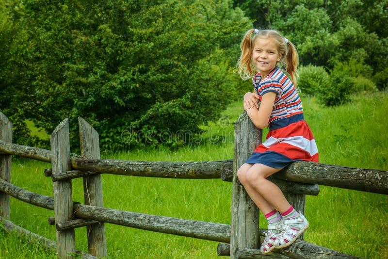 Petite fille de sourire s'asseyant sur la barrière en bois photos stock