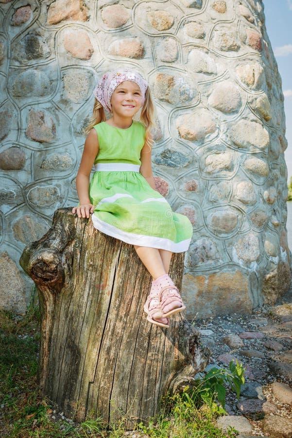 Petite fille de sourire s'asseyant sur le grand tronçon photo stock