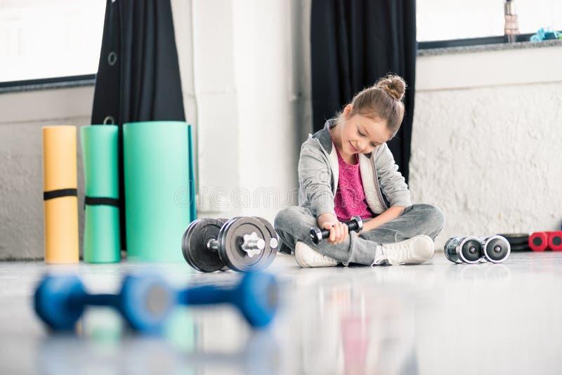 Petite fille de sourire s'asseyant sur le plancher et s'exerçant avec l'haltère dans le gymnase photographie stock
