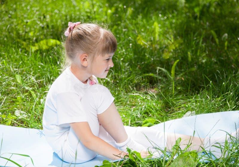 Petite fille de sourire se reposant en parc images stock